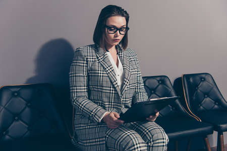 Pretty beautiful intelligent serious with trendy stylish hairdo holding checking she her lady in checkered plaid classic modern suit thoughtfully reading contract Stock Photo