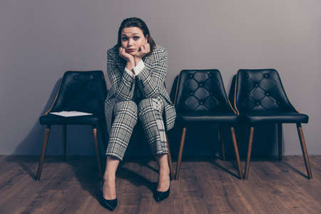 Full length size body photo of desperate she her lady sitting on black stylish designed armchairs waiting in line for meeting with new boss wearing checkered plaid suit high heels Stock Photo