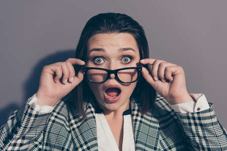 Closeup photo portrait of worried crazy unhappy upset sad she her lady holding touching specs on face with open mouth wearing collar checkered clothes suit isolated grey background Stock Photo