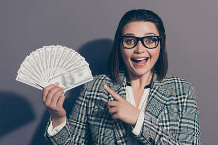 Close up photo portrait of laughing cheerful she her lady demonstrating many lot much money in hand looking at camera isolated grey background