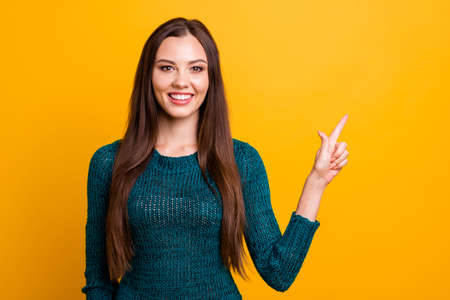 Close up photo beautiful her she lady white teeth long straight hair indicate arm finger empty space advising buy buyer new clothes prices wear green knitted pullover jumper isolated yellow background