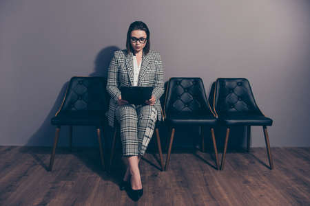 Full body length size photo portrait of serious concentrated focused smart clever intelligent she her lady using holding in hands clip board wearing checkered suit plaid costume Stock Photo