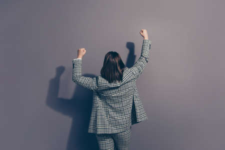 Rear back behind view photo of cheerful excited ecstatic confident employer raising fists hands up wearing fashionable checkered suit trousers isolated grey background