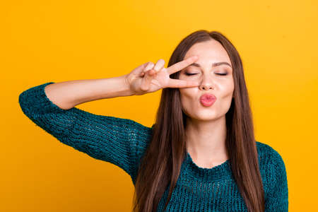 Close up photo beautiful funky her she lady arm hand fingers show v-sign near eye send people air kisses long straight hair wear jeans denim green knitted pullover jumper isolated yellow background