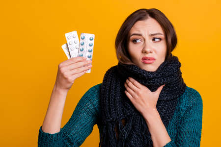 Close up photo beautiful her she model lady scarf around neck catch cold hold arm hand painful place packs pills picking harmful medicine wear green knitted pullover jumper isolated yellow background