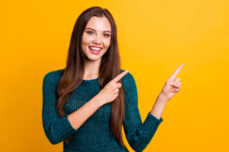 Close up photo beautiful her she lady white teeth indicate arm finger empty space advising buy buyer new clothes prices long straight hair wear green knitted pullover jumper isolated yellow background