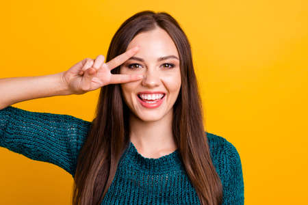 Close up photo beautiful her she lady arms hands fingers show v-sign near eye say hi friends relatives long straight hair wear jeans denim green knitted pullover jumper isolated yellow background
