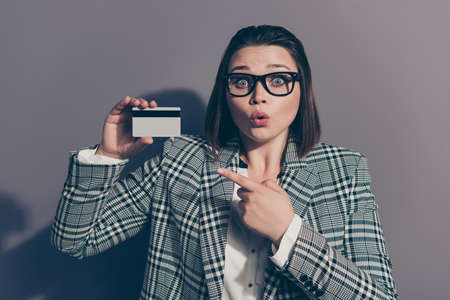 Closeup foto ritratto di stupita lei la sua signora che tiene mostrando la carta di plastica nelle mani indossando plaid a scacchi con giacca blazer giacca colletto isolato sfondo grigio