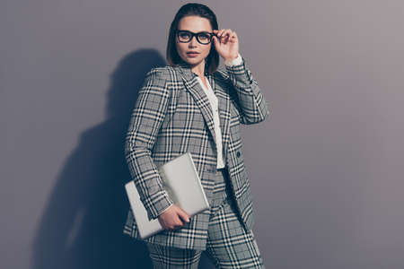 Portrait of graceful pretty intelligent attractive glad nice lovely thoughtful she her lady wearing classic plaid white jacket pants holding netbook in arm palm isolated grey background 版權商用圖片