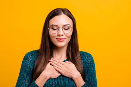 Close up photo beautiful her she lady long hair sweet hold hands arms close heart chest full feelings emotions wear specs casual dark green knitted pullover jumper clothes isolated yellow background