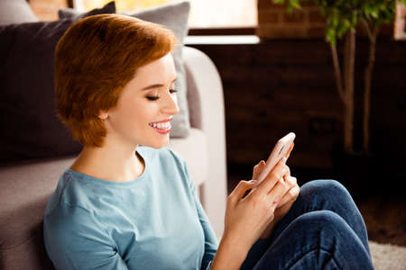 Close up side profile photo beautiful she her lady reader love letter hands telephone smart phone wear blue pullover jeans denim clothes sit floor fluffy carpet divan house loft living room indoors Banco de Imagens - 121963250