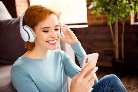 Close up photo beautiful she her lady hands telephone smart phone earflaps check choose audio track wear blue pullover jeans denim clothes sit floor fluffy carpet divan house loft living room indoors 版權商用圖片