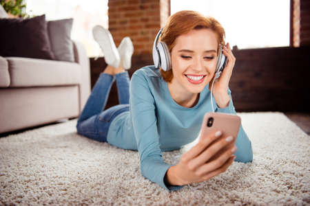Close up photo beautiful she her lady hands smart phone earflaps read words signing favorite songs wear blue pullover jeans denim clothes lying floor fluffy carpet divan house loft living room indoors