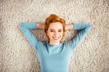 Bliska zdjęcie niesamowite piękne ona jej pani ręce ramiona za głową sen białe zęby czerwona krótka fryzura nosić niebieski sweter dżinsy denim ubrania leżące dywan podłoga tapczan dom na poddaszu salon w pomieszczeniu Zdjęcie Seryjne