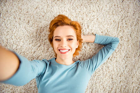 Close up photo amazing beautiful she her lady hands arms behind head make take selfies toothy smile wear blue pullover jeans denim clothes lying carpet floor divan house loft living room indoors 写真素材