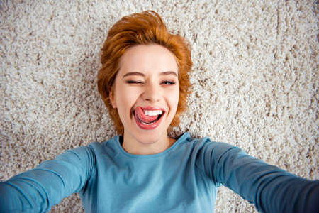 Close up photo beautiful she her lady hands arms make take selfies childish mood wink eye tongue out mouth wear blue pullover clothes lying carpet floor divan house loft living room indoors