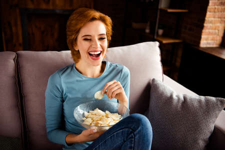 Close up photo beautiful she her lady hands arms plate crispy crunchy fried dry potato slices chip fast unhealthy food wear blue casual pullover jeans denim sit comfy divan house living room indoors