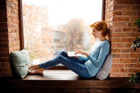 Close up side profile photo beautiful she her lady hands texting notebook foreign friends excited wear blue pullover jeans denim clothes sit comfy big large windowsill house loft living room indoors Stockfoto