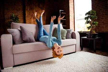 Full length body size photo beautiful she her lady hands arms legs raised upside down rejoicing having best day off wear blue casual pullover jeans denim sit comfy divan house living room indoors