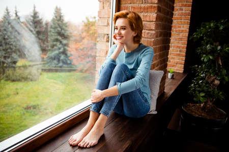 Photo pleine longueur de la taille du corps belle funky elle sa dame intérêt curieux se demandait grande fenêtre vue parfaite porter un pull bleu jeans vêtements en jean s'asseoir confortable sur le rebord de la fenêtre maison salon à l'intérieur