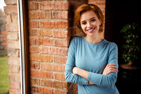 Close up photo beautiful funky she her lady lean wall curious interest wondered arms crossed wear blue pullover jeans denim clothes stand comfy near large window windowsill house living room indoors Stock Photo