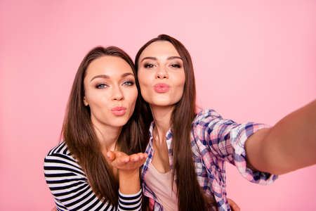 Self-portrait of nice attractive lovely lovable cute charming feminine winsome girlish cheerful straight-haired girls bonding sending kiss plump lips isolated over pink pastel background