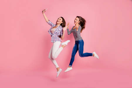 Hello world Full length body size view photo of positive cheerful girls students have free time weekends stylish holidays show make v-signs greet wear jeans shirts isolated on pink background