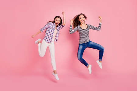 Full length body size view photo of lucky luck millennial ladies raising fists screaming yes yeah excited enjoying aims feeling playful on pink background isolated in denim colorful outfit