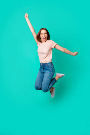 Full length body size photo beautiful amazing her she lady jumping high yell unexpected unbelievable success short hairdo wear casual jeans denim pastel t-shirt isolated teal turquoise background