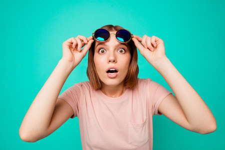 Close up photo beautiful funny funky her she lady take sunglass off oh no expression said wrong bad thing trip abroad danger wear specs casual pastel t-shirt clothes isolated teal turquoise background 版權商用圖片