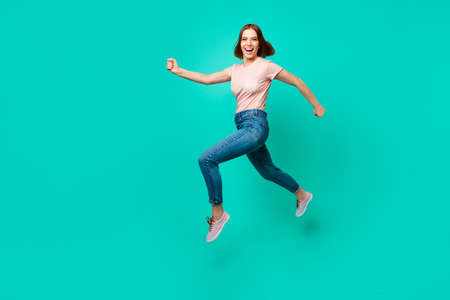 Full length side profile body size photo beautiful amazing her she lady flight jump high little prices rush hurry black friday wear casual jeans denim pastel t-shirt isolated teal turquoise background 写真素材 - 121965878