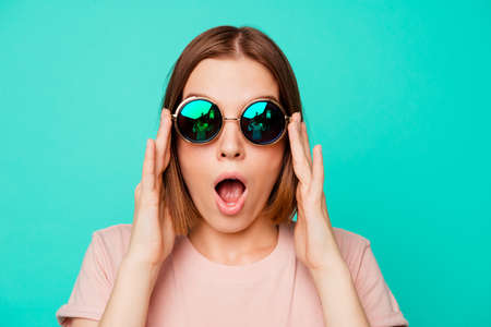 Close up photo beautiful funny funky her she lady hold sunglass oh no expression said wrong bad thing trip abroad danger wear specs casual pastel t-shirt clothes isolated teal turquoise background