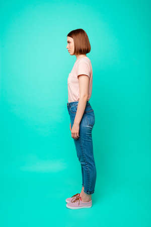 Full length side profile body size photo beautiful amazing her she lady look wondered not smiling empty space snapshot wear casual jeans denim pastel t-shirt isolated teal turquoise background