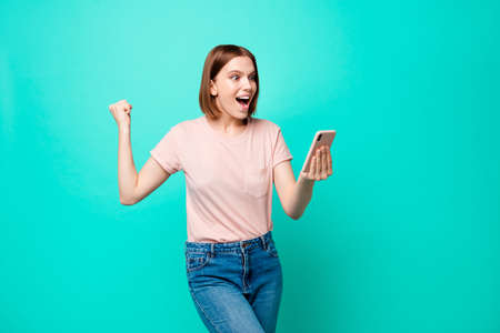Close up photo beautiful amazing her she lady toothy hands arms telephone great fortunate event lucky money income win sale discount shopping wear casual t-shirt isolated teal turquoise background Stock Photo