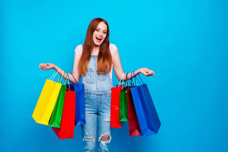 Close up photo beautiful amazing she her lady buy carry packing weekend shop mall store visiting black friday unbelievable prices wear casual jeans denim overalls clothes isolated blue background