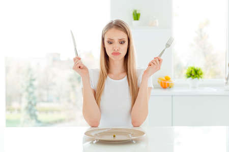 Portrait of irritated disappointed lady stressed beautiful trendy want much many food obsession use knife fork dish sit light kitchen wear modern outfit