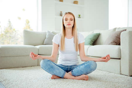 Portrait of serious lady millennial training yoga exercises meditative search tranquility sit floor lotus pose imagination beautiful couch divan dressed denim modern trendy outfit in living room