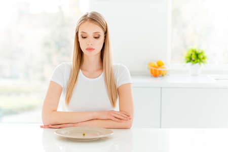 Portrait of strict minded pensive lady sad disappointed upset put arms table stare look dressed in modern clothes sit in light kitchen