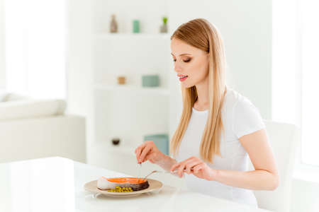 Portrait of calm positive millennial youth enjoy have dinner snack use fork knife eat delicious dish with proteins starving sit table chair in modern kitchen wear cotton t-shirts