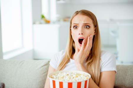 Nahaufnahme Foto von attraktiven netten Studentenjugend beeindruckt erstaunte Uhr sehen unglaubliche Fernsehprogrammunterhaltung schreien schreien berühren Wangen sitzen in einer hellen Wohnung, gekleidet in trendigem, modernem T-Shirt