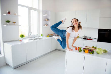 Full length body size view of her she nice-looking attractive bendy childish playful cheerful cheery wavy-haired girl having fun standing hands on table in modern light white interior style room