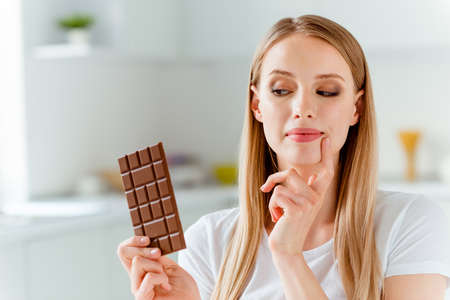 Close-up portrait of her she nice-looking cute charming lovely attractive cheerful girlish foxy straight-haired girl wearing white tshirt looking at choco bar in light white interior room