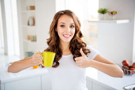 Close-up portrait of her she nice-looking cute attractive lovely winsome cheerful wavy-haired girl wearing casual drinking green tea showing thumbup in modern light white interior style room