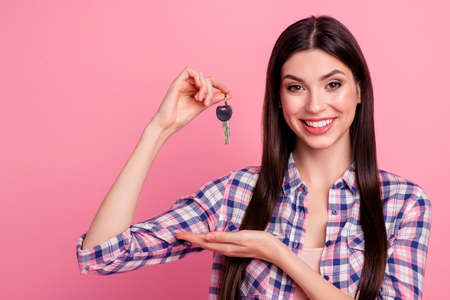 Close-up portrait of her she nice-looking attractive cute charming shine lovely cheerful straight-haired lady holding in hands keys from new apartment isolated over pink pastel background