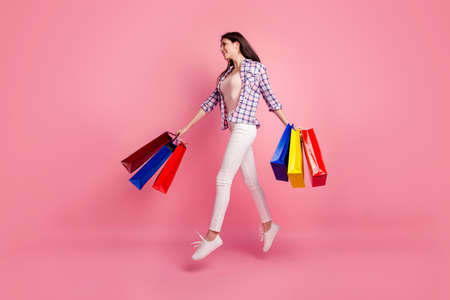 Full length side profile body size photo beautiful her she lady jump high hands arms purchase amazed motion wear shoes hat casual checkered plaid shirt white jeans denim isolated pink background