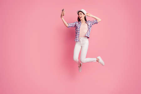 Full length side profile body size photo beautiful her she lady jump high telephone hand arm make take selfies wear shoes hat casual checkered plaid shirt white jeans denim isolated pink background