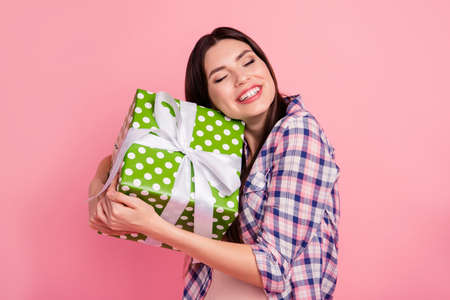 Close-up portrait of nice attractive cute charming lovely cheerful straight-haired lady wearing checked shirt holding in hands hugging big large green cool box isolated over pink background