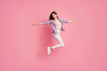 Full length side profile body size photo yell beautiful her she lady jump high competition cheerleader wear shoes casual checkered plaid shirt white jeans denim clothes isolated pink background Stock Photo