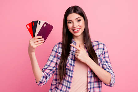 Portrait of her she nice-looking attractive cute charming lovely cheerful straight-haired lady holding in hands showing cool new fashionable cases sale discount ad isolated over pink background