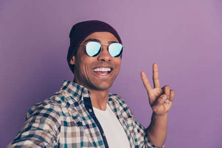 Close up photo portrait of cool handsome attractive  optimistic guy making video call to friends showing v-sign white teeth isolated violet background